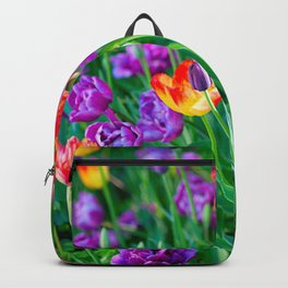 Colorful Tulip Flowers On A FLowerbed. Green Leaves And Stems Backpack
