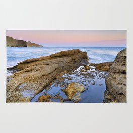 """""""Volcanic sea at pink sunset"""" Rug"""