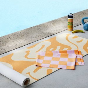 smiley face patterned yoga mat and checkered yoga towel next to a pool