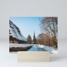 Heavy snow on a street in a traditional Romanian village Mini Art Print