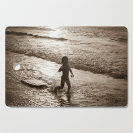 Little surfer girl runs in the waves with her bodyboard Cutting Board