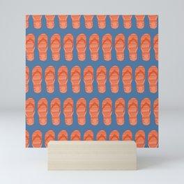 Orange flip flop shoes on a blue background. Mini Art Print