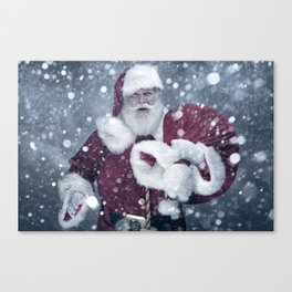 Santa Claus walking thru a winter snow storm to deliver Christmas Gifts Canvas Print