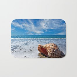 Beach with conch shell under blue sky Bath Mat