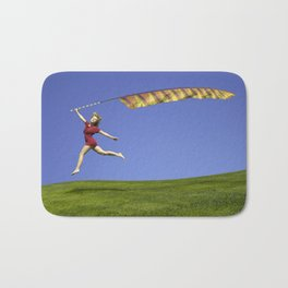 Freedom - A young girl jumping with a colorful kite banner on a clear blue sky day Bath Mat