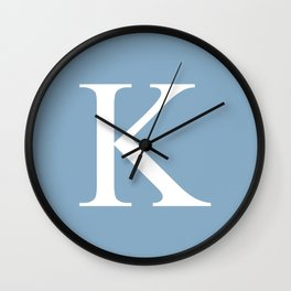 Letter K sign on placid blue background Wall Clock