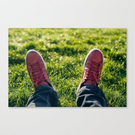 Man feet wearing red leather sport shoes on green grass Canvas Print