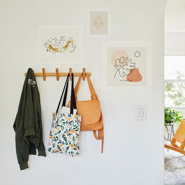 tote bag with orange print hanging on wall