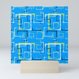 White and yellow carved squares and black frames for an abstract blue background or pattern. Mini Art Print