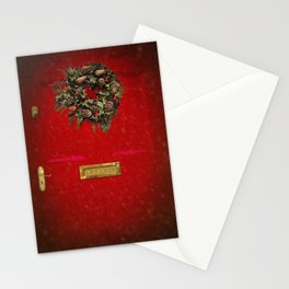 Christmas decorative wreath hung on red Victorian door with winter snow. Stationery Cards