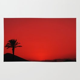 Red Andalusian sunset with silhouette palm tree and mountain Rug