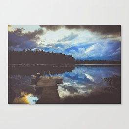 dramatic storm clouds reflecting over a lake with a dock Canvas Print