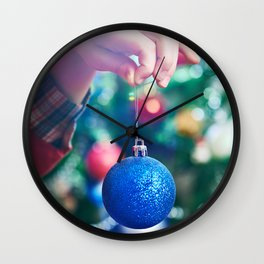 Children's hand with blue Christmas toy ball Wall Clock