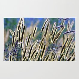 tall grasses with seeds with blue sky and sunny day Rug