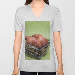 Macro shoot of croissants in shopping basket over green mint background Unisex V-Neck