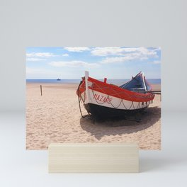 Fishing boat on the shores of the atlantic ocean in the village Nazare, Portugal Mini Art Print