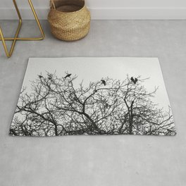 A murder of crows sitting in a tree Rug