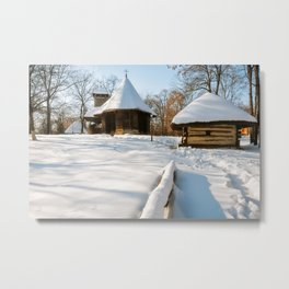 Snow cover in a Romanian Village with an old wooden church Metal Print