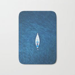An aerial view of a sailing boat surrounded by blue ocean water Bath Mat