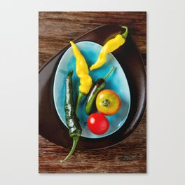 Ripe red cherry tomatoes on a blue plate. Dark wood background. Top view Canvas Print
