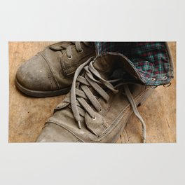 Pair of old leather shoes, worn-out and dusty, on wooden background Rug