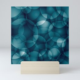 Dark intersecting heavenly translucent circles in bright colors with the blue glow of the ocean. Mini Art Print