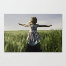 A little girl dancing in a field of barley Canvas Print