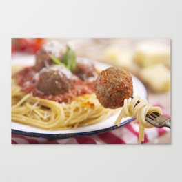Spaghetti and meatball on a fork, plate in the background Canvas Print