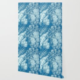 Fluffy clouds in a blue sky Wallpaper
