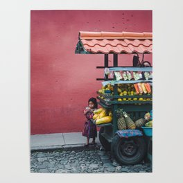 Young Guatemalan girl in traditional Mayan dress watches the street from behind a fruit stall cart Poster