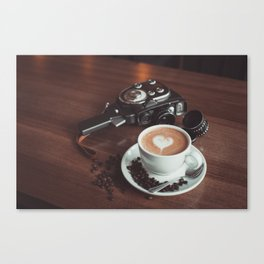 A cup of hot cappuccino placed on a table next to the old camera with lens and coffee beans Canvas Print