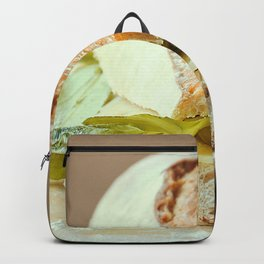 Baguette cut in two, bitten, stuffed with cheese, salad, baked ham Backpack