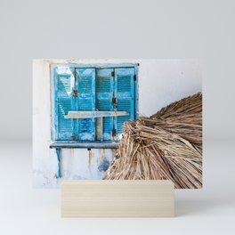 Distressed Blue Wooden Shutters and Beach Umbrella in Crete. Mini Art Print