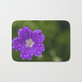A Cranesbill Geranium blooms in a Spring Rainshower Bath Mat