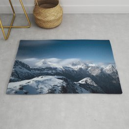 Clouds rolling above snowy mountains Rug