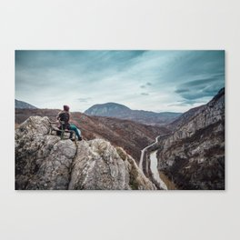 Girl sitting on the bench on the edge of the canyon with amazing view in front of her Canvas Print