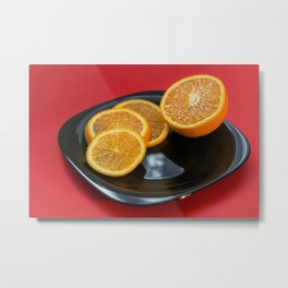 Sliced orange on the black plate and red background Metal Print