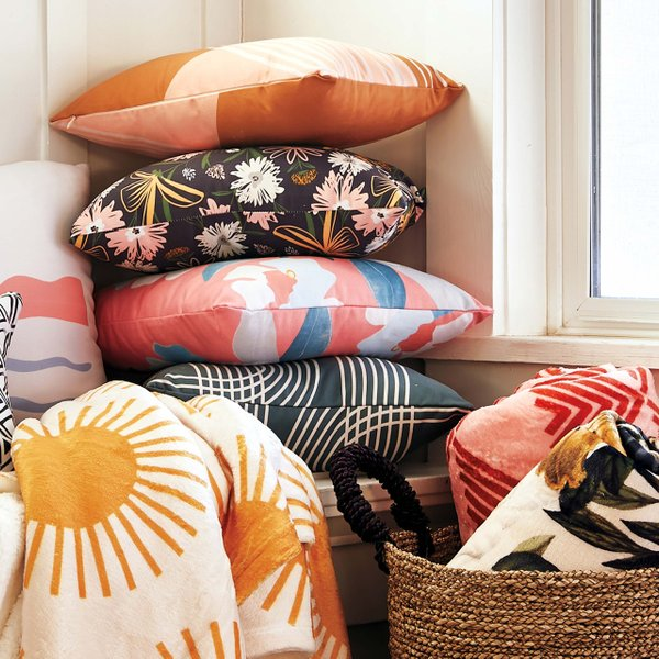stack of pillows and blankets in sunlit corner