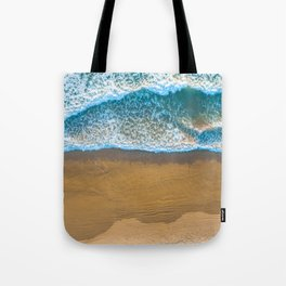 Ocean waves crash into the shore at sunset - aerial view Tote Bag