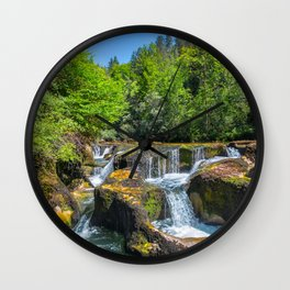 Rock erosion from waterhole with waterfall in middle of forest Wall Clock