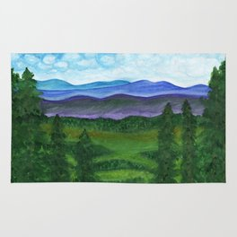 View from a mountain slope to distant mountains and forests Rug