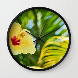 Yellow and Red Hibiscus Flower on green fern background Wall Clock