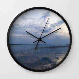 Sunlight in the cloudy blue sky is reflected in the clear spring water of the lake at sunset Wall Clock