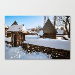 Traditional handcrafted gate and a rural Romanian homestead covered in snow Canvas Print
