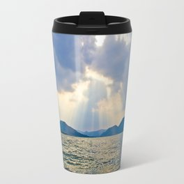 Rays of sunlight shining through the clouds down on a calm ocean Travel Mug