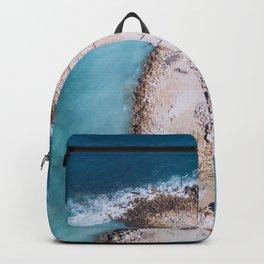 ocean waves crashing on small island aerial Backpack