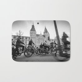 Cyclists ride in Amsterdam street in front of the Rijksmuseum Bath Mat