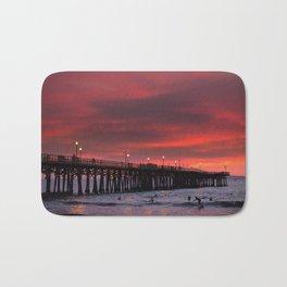 Surfers riding waves off Seal Beach pier at sunset Bath Mat