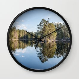 Scandinavian summer landscape with forest and reflections in lake Wall Clock