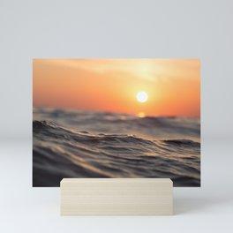 Calm sea with distant sunset Mini Art Print